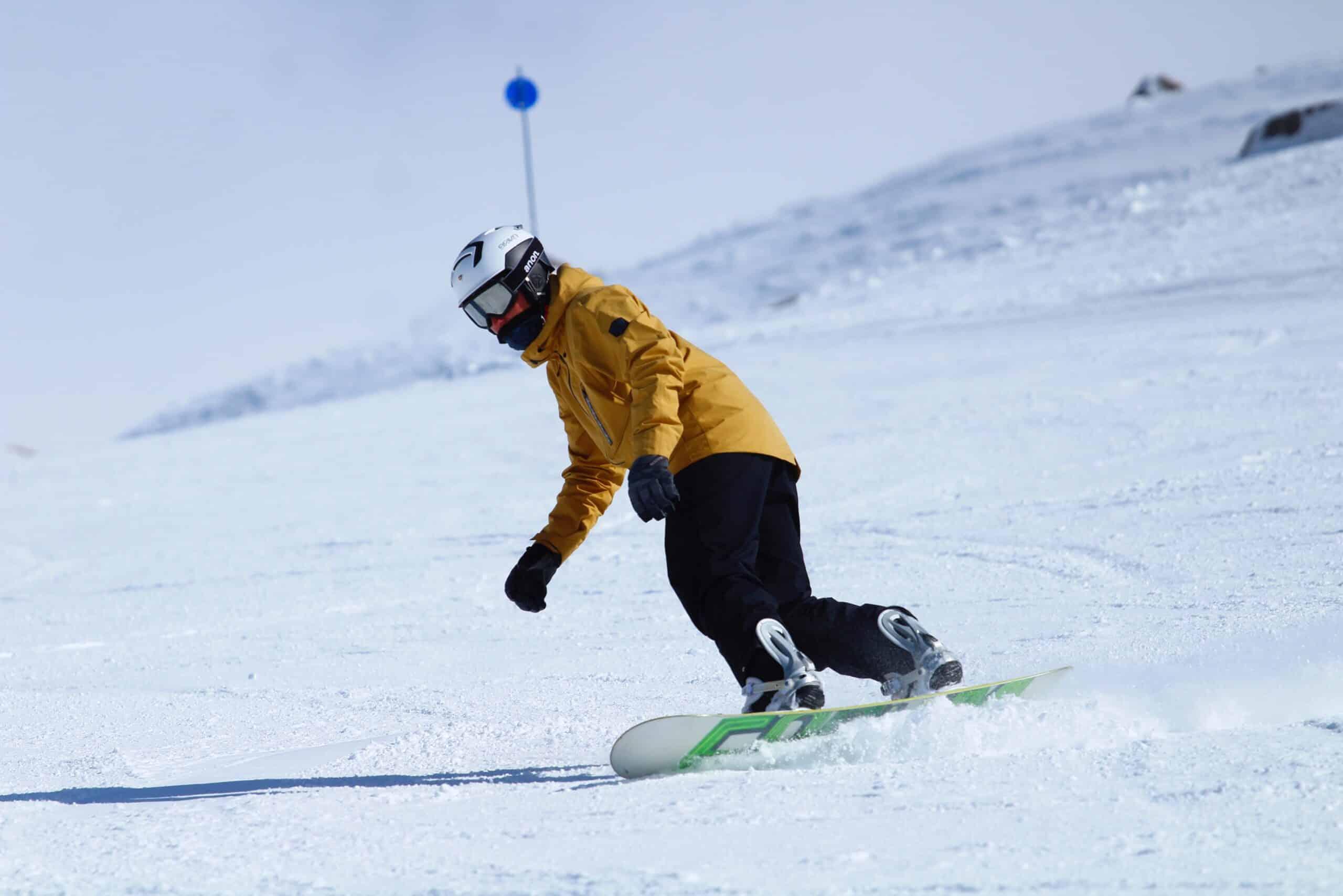 man turning on snowboard