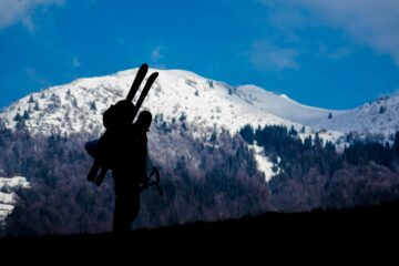 man carrying skis with straps