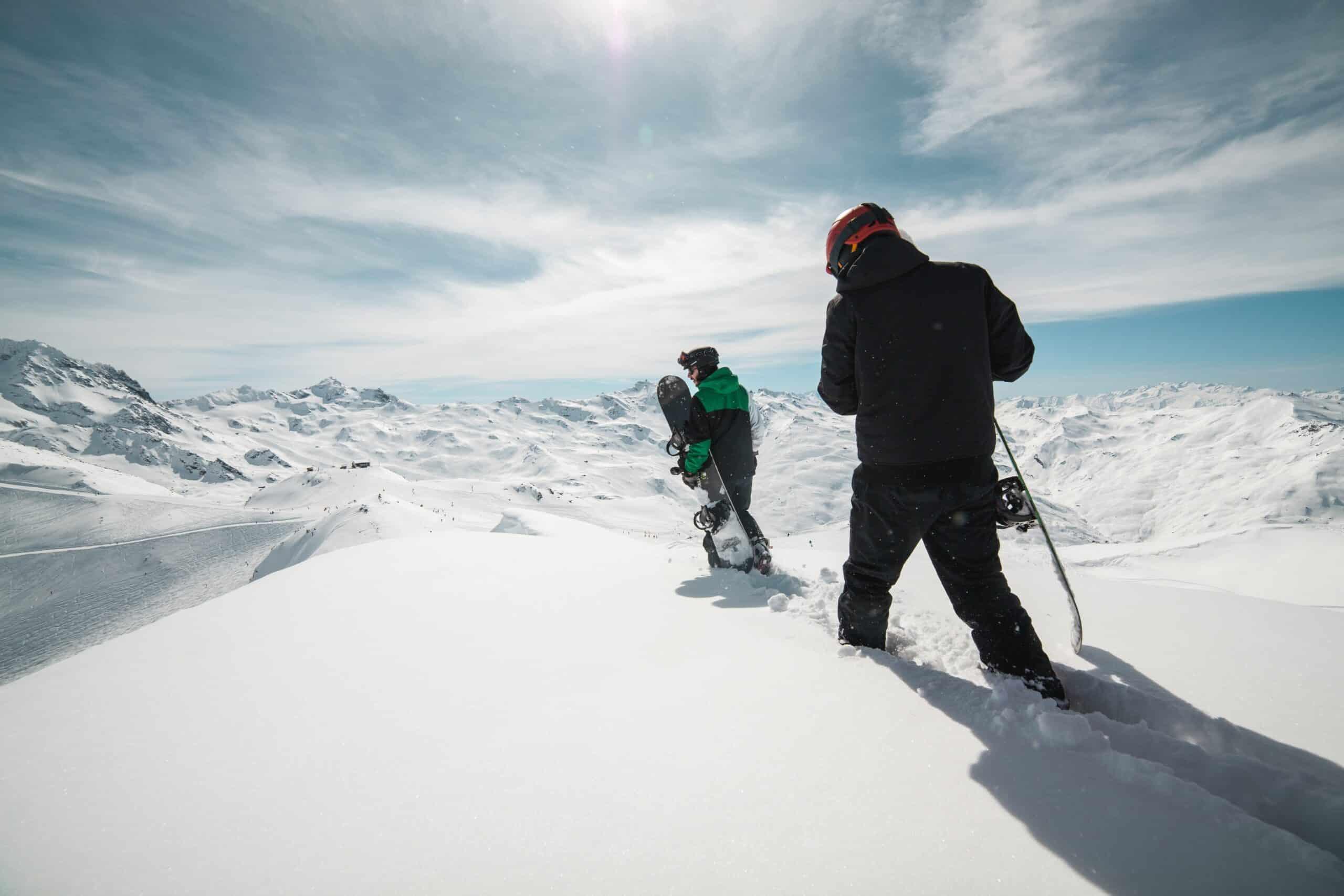 man teaching kid to snowboard